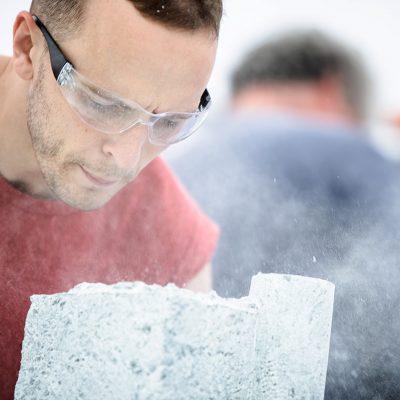 Joe Milne (29) blåser vekk steinrester fra steinslottet som han skjærer ut. Han jobber fulltid som steinfagarbeider i England. Dette er en av de få arenaene hvor han kan utforske sin kunstneriske side.